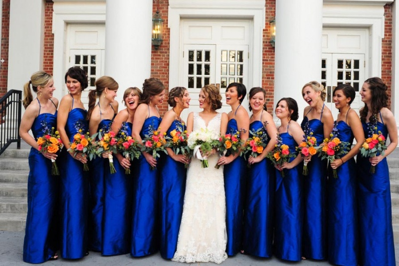 mxcp46-bridesmaids-looking-at-bride-smiles-laughing-holding-bouquets-outside-church