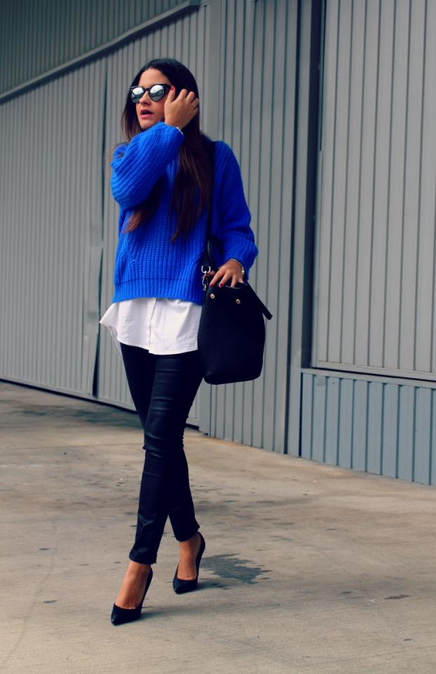 jersey azul con camisa blanca y tacones negros. Gafas espejo plata negro.